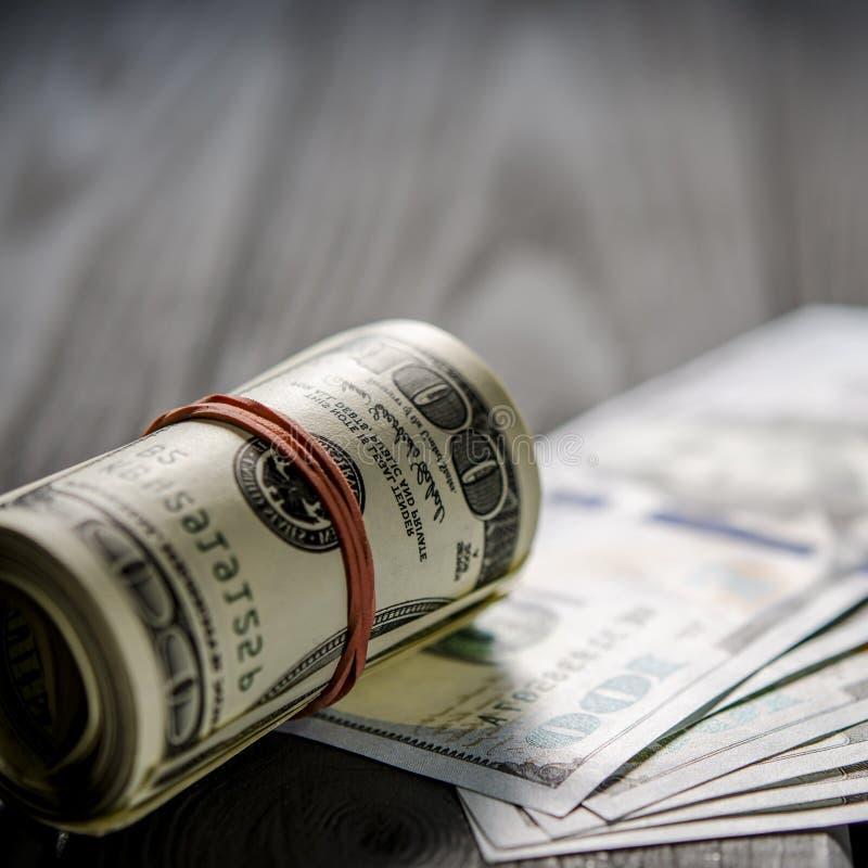 Толстый крен старых 100 банкнот доллара связал красную круглую резинку лежит на вискере новых 100 долларовых банкнот стоковые изображения rf