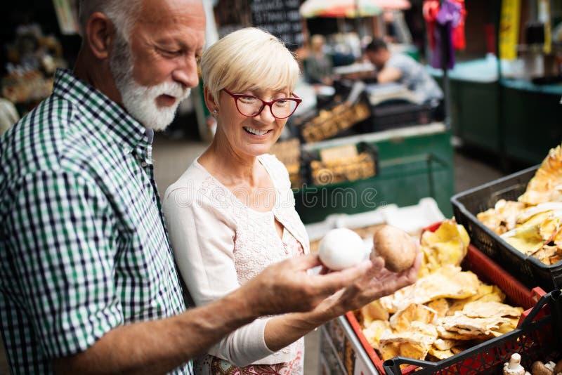 Только самые лучшие фрукты и овощи Свежие продукты красивых старших пар покупая на рынке стоковое изображение