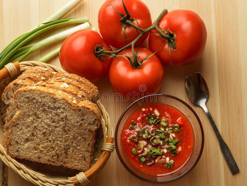 Томатный соус в стеклянном шаре, свежем хлебе, луке на деревянном столе, ингридиентах соуса для домодельной вегетарианской еды, в стоковые изображения rf