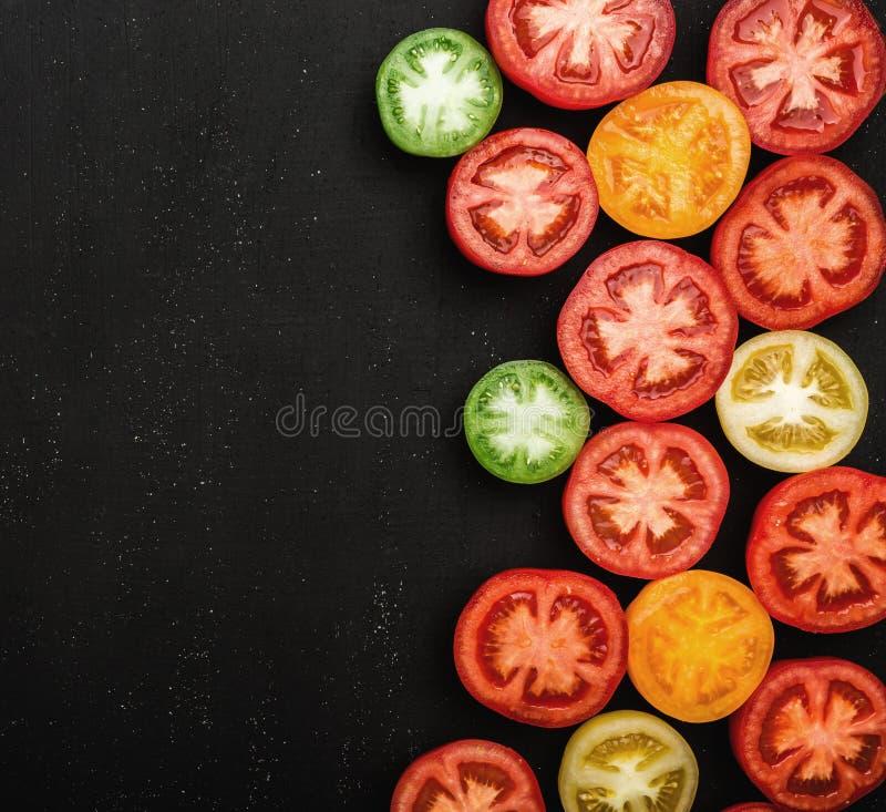 Томаты других цветов отрезанных в половине Свежие и сочные овощи на черной каменной предпосылке, взгляд сверху стоковые фото