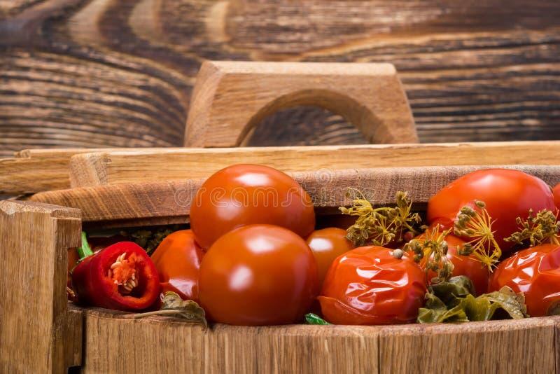 Томаты и condiments в бочонке под крышкой, деревянной предпосылкой стоковые изображения rf