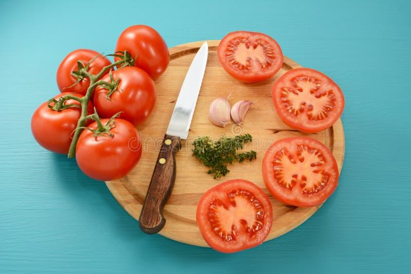 Томаты отрезали для жарить в духовке с ножом, чесноком и тимианом стоковое фото rf