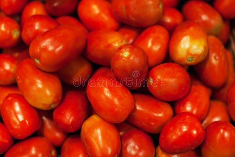томаты предпосылки свежие Органические зрелые красные томаты в рынке стоковая фотография