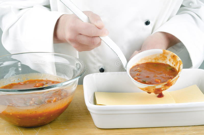 томат соуса уполовника шеф-повара женский стоковые изображения rf