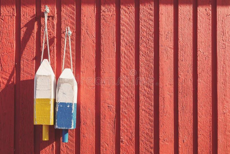 Томбуи рыбной ловли на красной деревянной стене, горизонтальной стоковая фотография rf