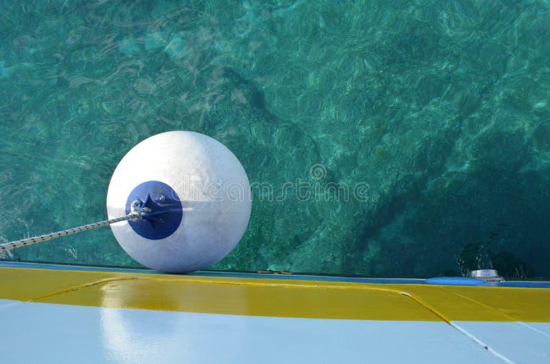 Томбуй маленькой лодки в голубой и cyan покрашенной воде стоковое изображение rf