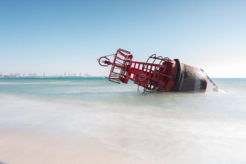 Томбуй навигации, который сели на мель на пляже сильные токи шторма с длинной экспозицией для влияния шелка стоковое фото rf