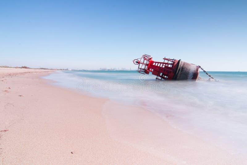 Томбуй навигации, который сели на мель на пляже сильные токи шторма с длинной экспозицией для влияния шелка стоковое фото