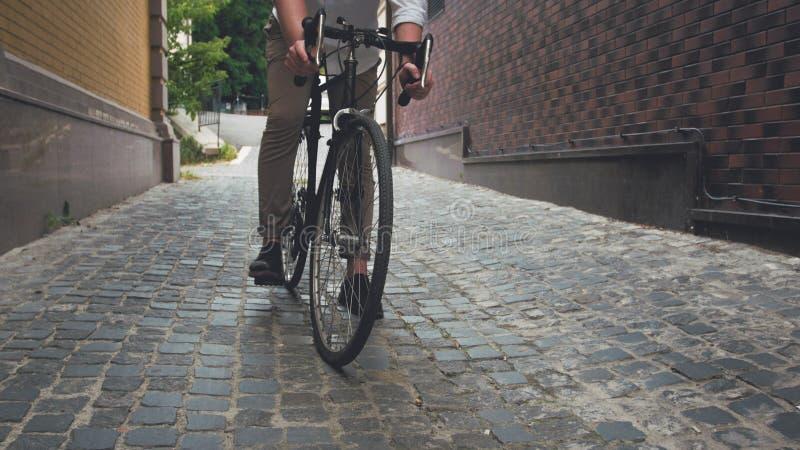 Тонизированное изображение велосипеда стильного катания молодого человека винтажного на вымощенной дороге стоковая фотография rf