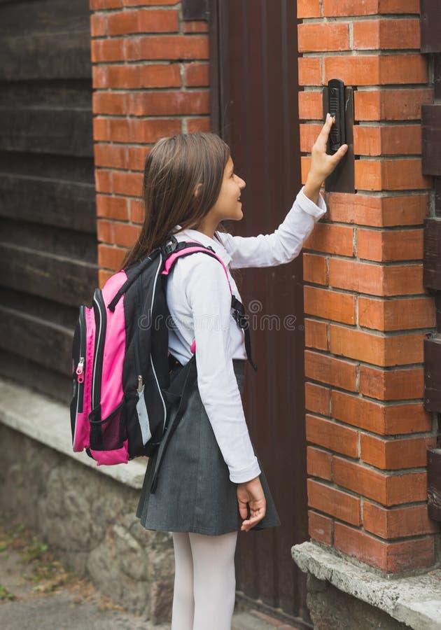 Тонизированное изображение девочка-подростка в школьной форме звеня в дверном звонке стоковое изображение