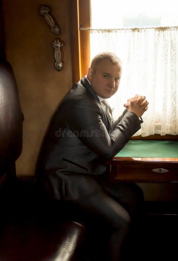 Тонизированный портрет бизнесмена путешествуя в старом поезде стоковые фото