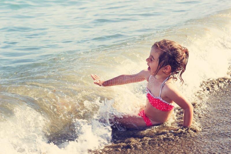 Тонизированный портрет милой маленькой девочки усмехаясь на пляже океана стоковые изображения rf