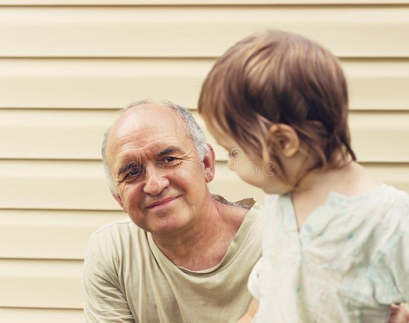 Тонизированный портрет счастливого деда и grandaughter играя на стоковое изображение