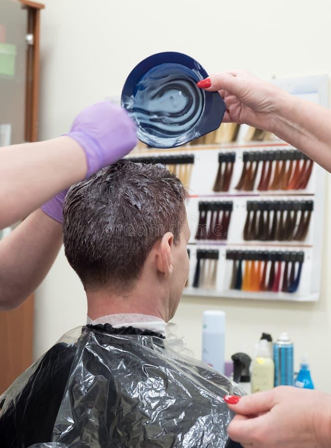 Тонизировать серые волосы на голове человека в салоне красоты стоковая фотография rf