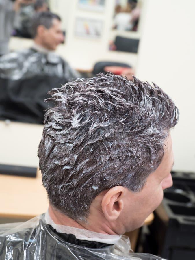Тонизировать серые волосы на голове человека в салоне красоты стоковое фото rf