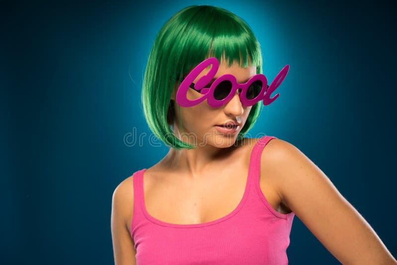 Тонкая дама в зеленых волосах нося розовое безрукавное стоковое фото rf