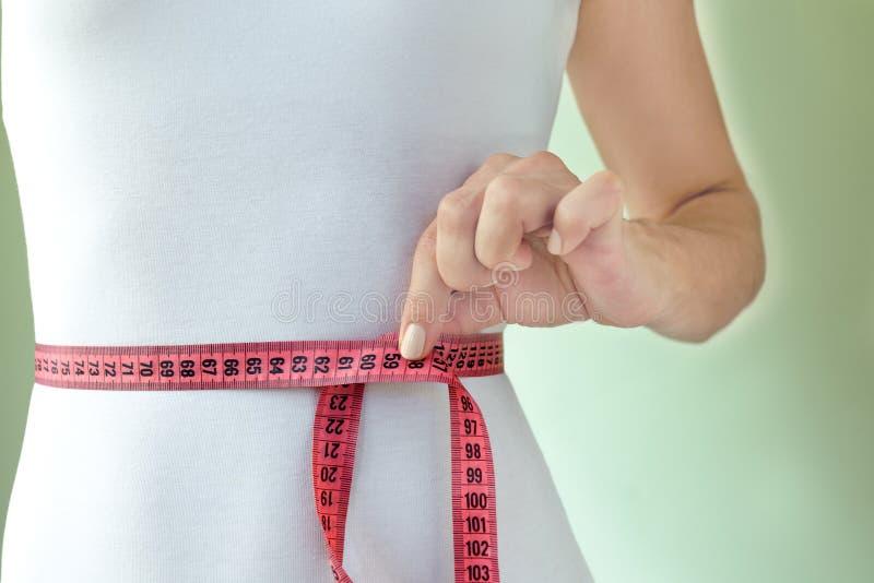Тонкая атлетическая женщина в белом тощем купальнике измеряет талию с измеряя лентой стоковые фото