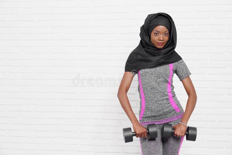 Тонкая африканская мусульманская женщина с гантелями стоковое фото rf