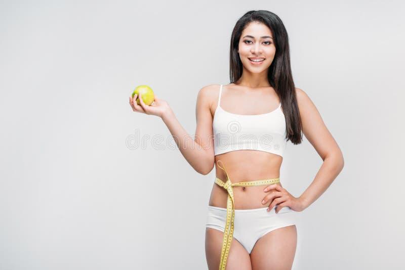 тонкая Афро-американская девушка в белом женском белье с измеряя лентой на яблоке удерживания талии стоковые изображения