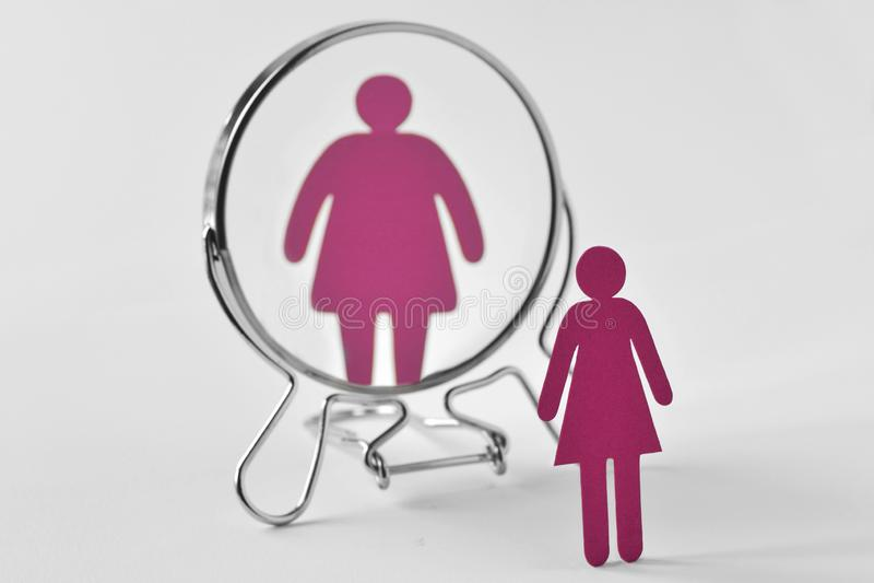 Тонкая бумажная женщина смотря в зеркале и видя как жирная женщина - анорексия и концепция расстройств пищевого поведения стоковые изображения rf