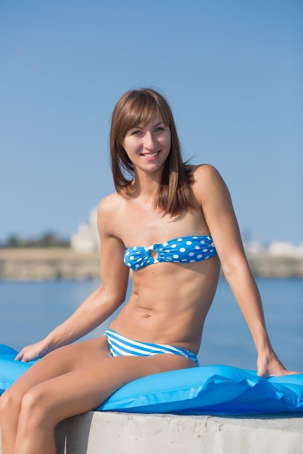 Тонкая высокорослая девушка в голубом бикини на море стоковое изображение rf