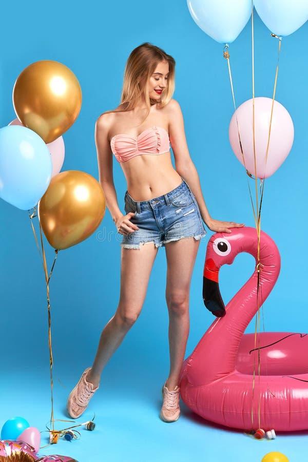 Тонкая грациозная очаровательная девушка с длинной блондинкой смотря раздувной фламинго стоковая фотография