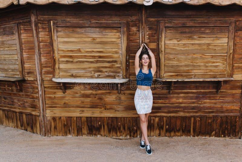Тонкая грациозная стильная дама околпачивая вокруг около деревянного стойла, касаясь ее волосам и стоя на подсказк-пальцах ноги Б стоковые изображения rf