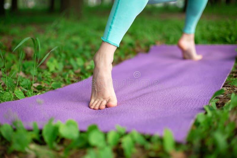 Тонкая девушка брюнета играет спорт и выполняет представления йоги в парке лета Зеленый лес на предпосылке Женщина делая трениров стоковая фотография rf