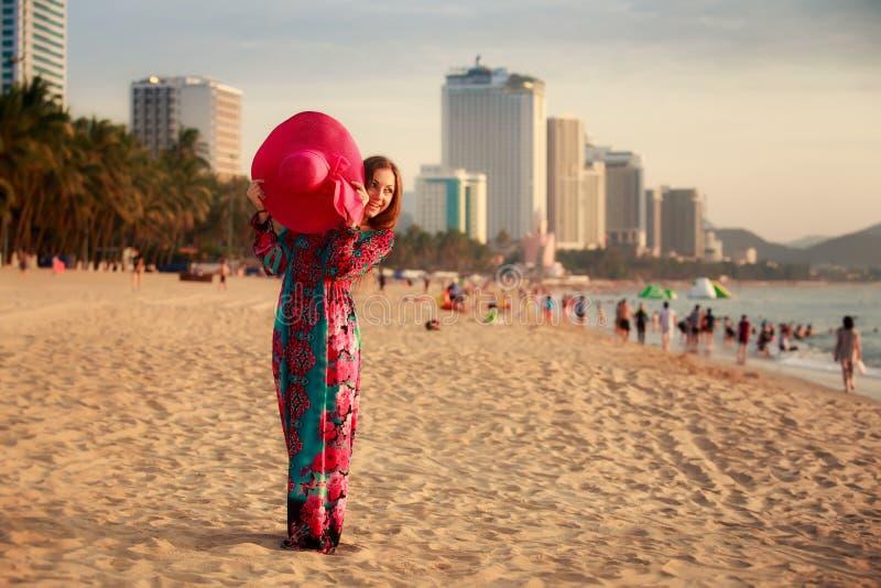 тонкая девушка в шляпе длинными владениями большой на пляже против моря города стоковые изображения rf