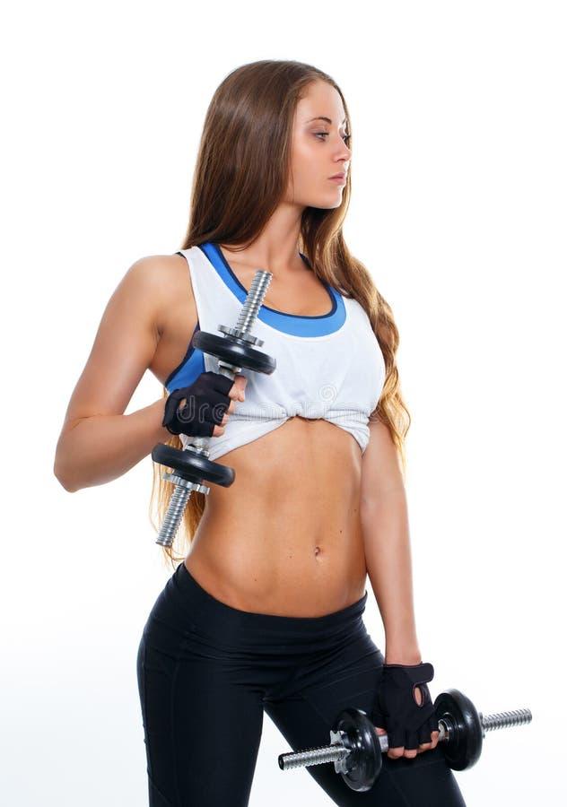Тонкая женщина в sportswear держа пары dumbells стоковые фото