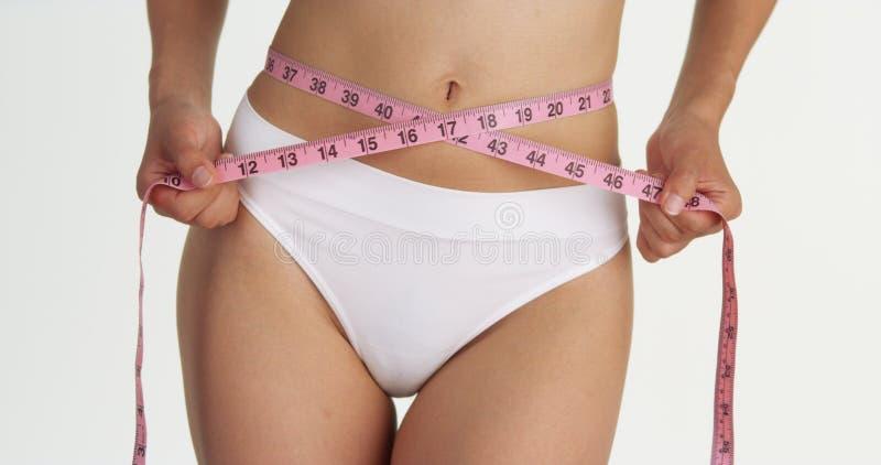 Тонкая женщина измеряя ее талию с лентой стоковые фото