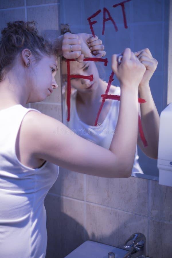 Тонкая женщина ненавидя ее тело стоковое фото rf