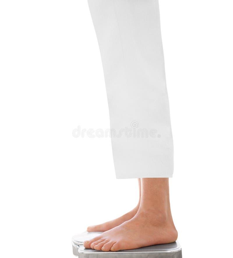 Тонкая женщина стоя на весе стоковые фото