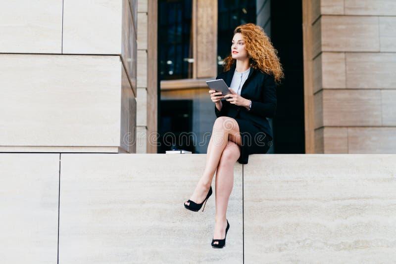 Тонкая коммерсантка с волнистыми роскошными волосами, имеющ худенькие ноги, нося черный элегантный костюм и ботинки, держа планше стоковые фотографии rf