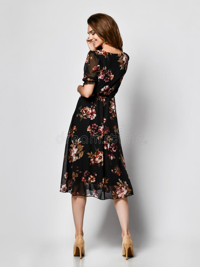Тонкая курчавая женская модель стоит назад в росте платья шелка бледном темном полностью Милая девушка в романтичных одеждах идет стоковые изображения