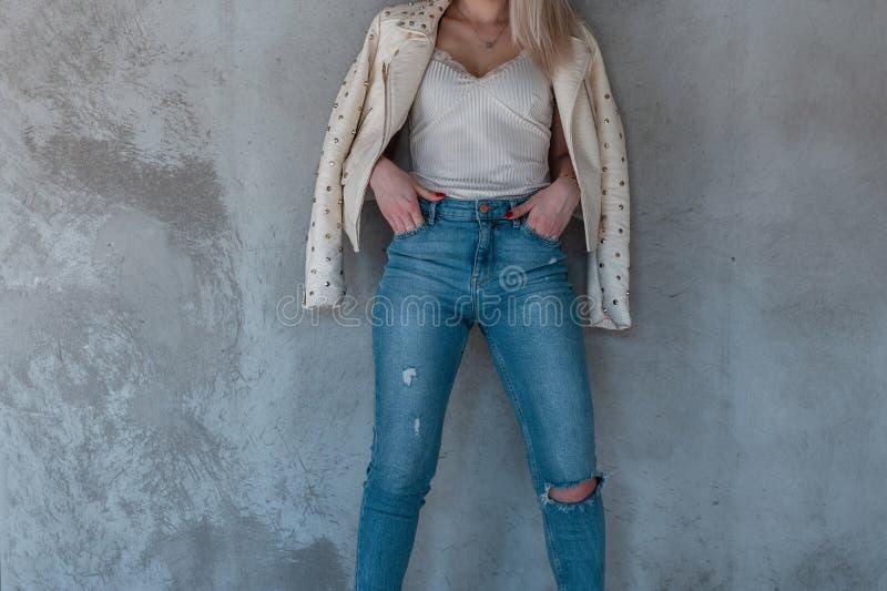 Тонкая модель молодой женщины представляя около серой стены в модных одеждах молодости Новое собрание весны одежды стильных женщи стоковое фото rf