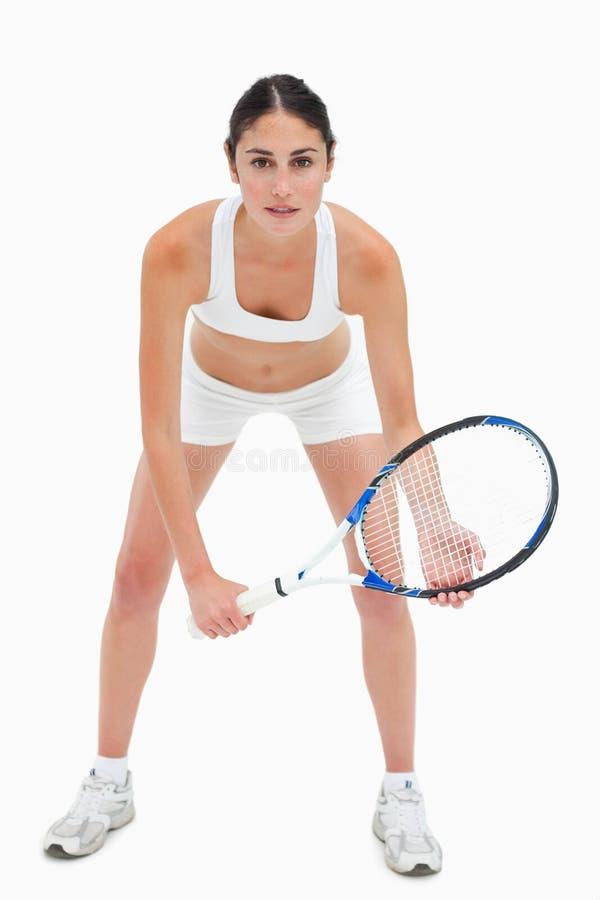 Тонкая молодая женщина играя теннис в белых одеждах стоковые изображения rf