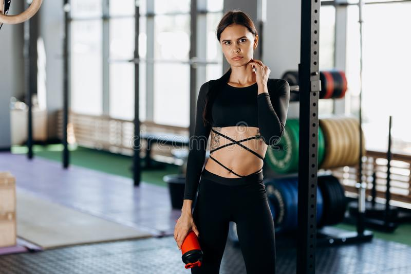 Тонкая темн-с волосами девушка одетая в черных стойках sportswear с водой в ее руке около оборудования спорта в спортзале стоковая фотография rf