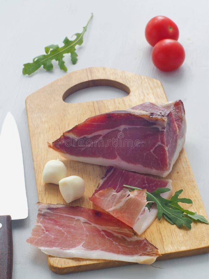 Тонкая часть плоти на белой таблице Ветчина, prsut, или испанское jamon с томатами вишни, свежим arugula и моццареллой стоковое изображение rf