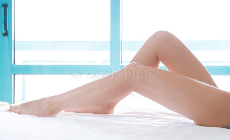 Тонкие красивые женские ноги на кровати Подрезанное изображение эротично лежать на женщине кровати красивой в спальне Скомканные  стоковое фото