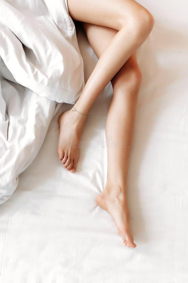 Тонкие, совершенные и красивые пересеченные ноги женщины на кровати стоковое изображение