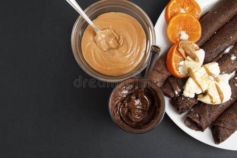 Тонкие чувствительные блинчики шоколада, свернутые с плодоовощами и сливк Темная предпосылка помадка завтрака стоковые изображения