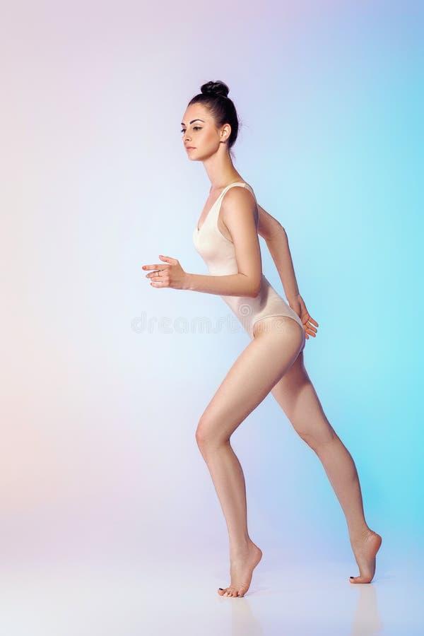 Тонкий гимнаст в бежевом купальнике стоковая фотография rf