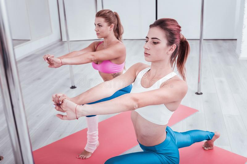 2 тонких красивых женщины посещая студию танца поляка на их выходных стоковые фото