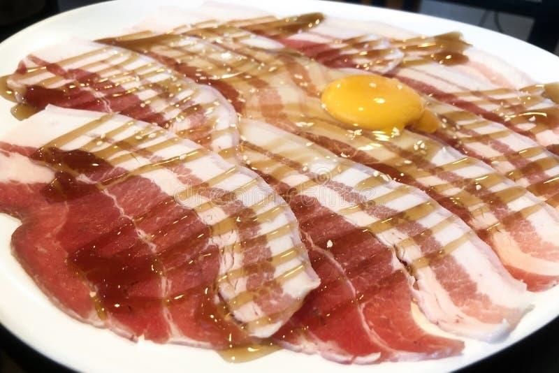 Тонкое отрезанное мясо свинины в черной плите подготовленной для shabu или sukiyaki стоковые фото