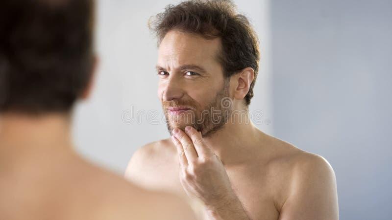 Топлесс мужчина критически смотря его бороду в зеркале, ритуале утра, bathroom стоковое фото