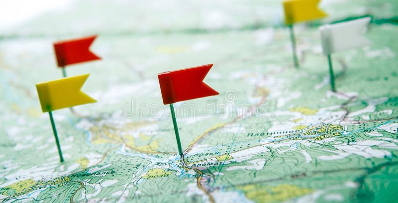 Топографическая карта с покрашенными pushpins флага закрывает вверх стоковые фотографии rf