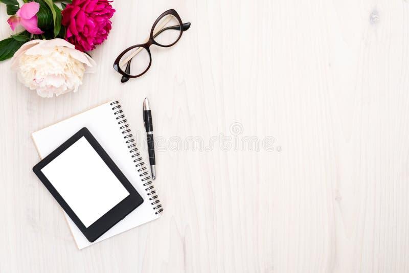 Топ-вид E-reader, бумажная блокнота, очки и перо на деревянном фоне Жилые туалетные принадлежности, женский стол с электронной кн стоковое изображение