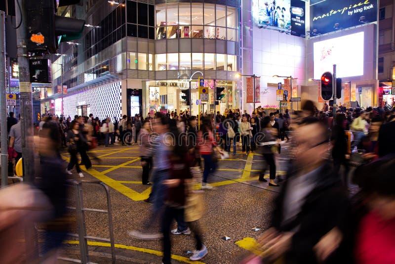 Торговая улица в Гонконге и пересечение дорог на ноче толпились с пешеходами стоковое изображение