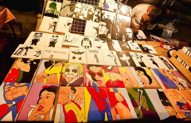 Торговец искусства надувательства рынка ночи много красочных изображений шипучк-искусства с героями кино и шаржа стоковая фотография